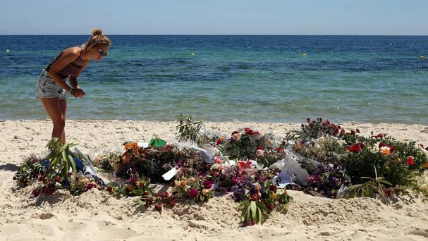 Tourists look at flowers that have been laid on the beach near the RIU Imperial Marhaba hotel in Sousse, Tunisia
