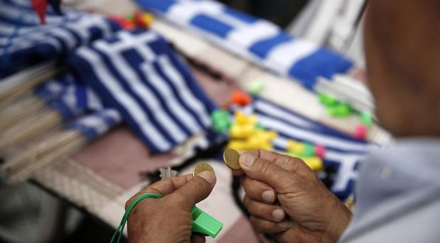 A man buys a Greek flags during a rally organized by supporters of the YES vote to the upcoming referendum (AP)