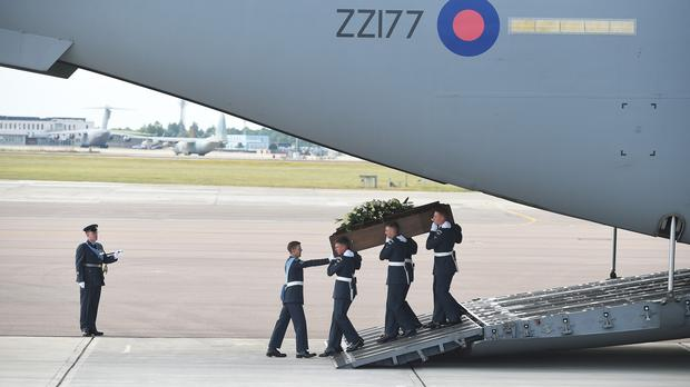 The coffin of Charles Evans is taken from the RAF C-17 carrying the bodies of eight British nationals killed in the Tunisia terror attack at RAF Brize Norton in Oxfordshire