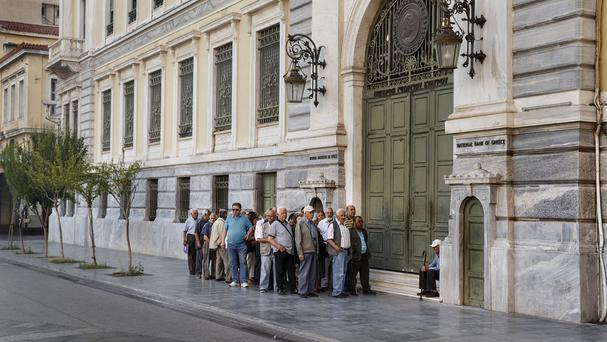 Greek pensioners line up as they wait to be allowed into a bank (AP)