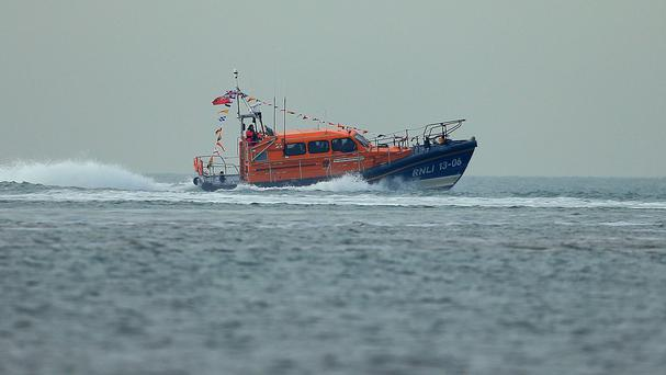 The RNLI rescued the man off Tywyn, Gwynedd, but he later died