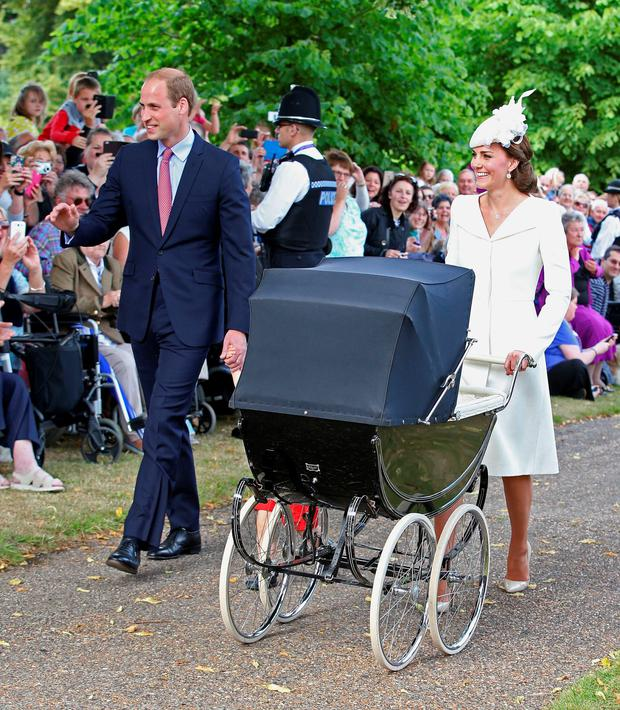 The Duchess of Cambridge, Prince William and Prince George arrive with Princess Charlotte in a traditional pram at the Church of St Mary Magdalene yesterday