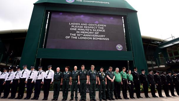 Members of staff working within the Wimbledon grounds observe a minute's silence to commemorate the tenth anniversary of the July 7 terrorist attacks