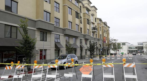 Police tape blocks off a section of Kittredge Street in front of the apartment building where balcony collapsed in Berkeley, California (AP)