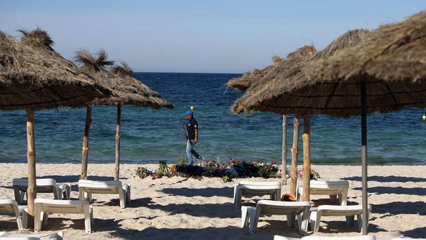 An armed policeman patrols on the beach after 30 Britons died in an attack by a gunman in Sousse