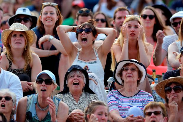 Spectators on Murray Mound react as they watch a giant screen showing the men's semi-final between Roger Federer and Andy Murray yesterday