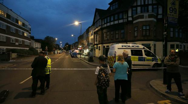 Emergency services at the scene in Wood Green, north London, as a man has died and a woman is in hospital following a suspected double shooting