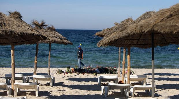 An armed policeman patrols on the beach near the RIU Imperial Marhaba hotel in Sousse, Tunisia