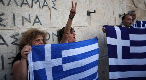 Anti-austerity protesters hold Greek flags as they shout slogans during a rally against the government's agreement with its creditors in Athens (AP)