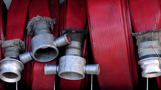 A hose was used to spray water down the trouser leg of a firefighter while he was suspended upside down from a tower in an initiation ceremony, a court heard