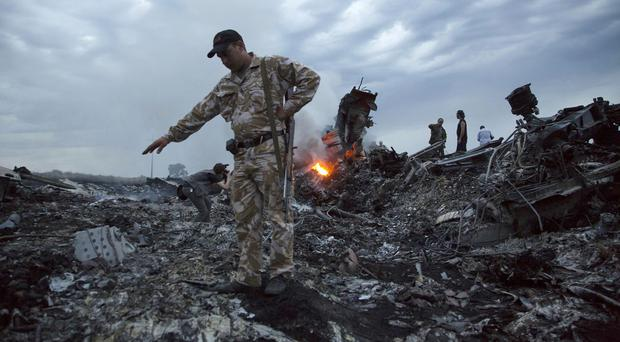 People walk among the debris at the crash site of the passenger plane near the village of Grabovo, Ukraine (AP)