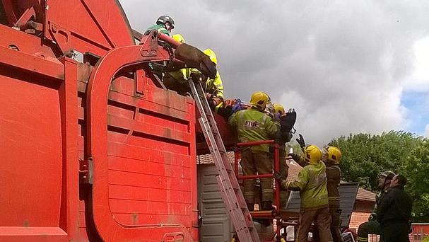 Paramedics rescuing a man found inside a bin lorry in Warwickshire (West Midlands Ambulance Service/PA)