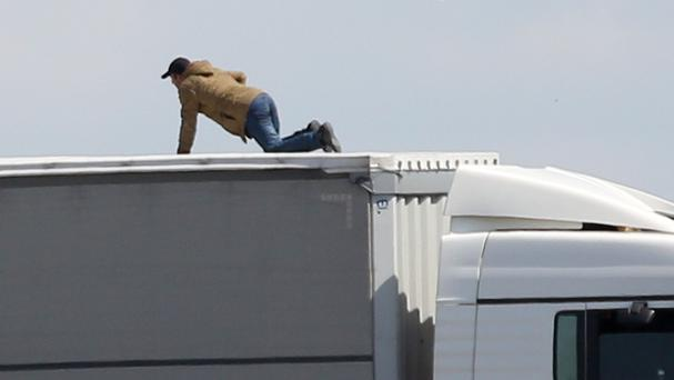 A migrant trying to board UK bound lorries on the main road into Calais ferry port (PA/file)