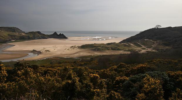 A man has died and a boy needed hospital treatment after a rescue at Three Cliffs Bay, South Wales