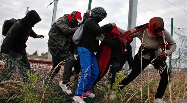 Migrants breach a fence as they escape from railway police in Calais (AP)