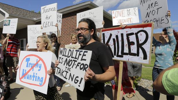 Protesters gather outside Dr Walter Palmer's dental surgery in the US (AP)