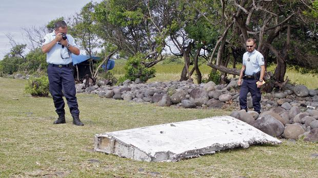 French police officers look over a piece of debris from a plane in Saint-Andre, Reunion Island (AP)