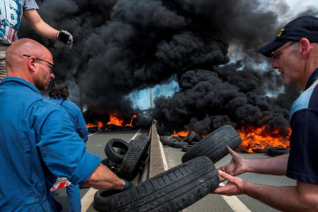 Ferry workers burn tyres on both lanes of a road leading to Calais yesterday as part of an ongoing dispute over job losses