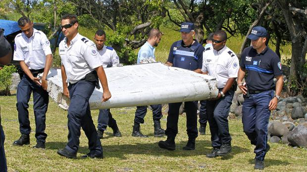 French police officers carry a piece of debris from a plane on Reunion island (AP)