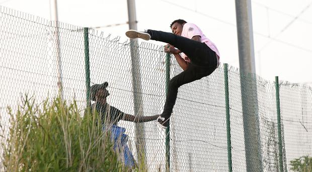 Migrants climb over a fence on to the tracks near the Eurotunnel site at Coquelles in Calais, France