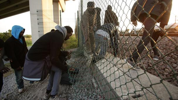 Migrants climb through a fence on to the tracks near the Eurotunnel site at Coquelles in Calais