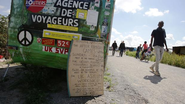 A notice outside a caravan advertises sporting activities and a UK asylum workshop for residents of the migrant camp known as the new Jungle in Calais