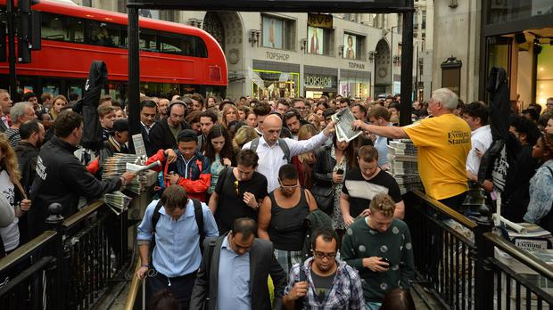 People queue at an entrance to Oxford Circus station as workers try to get home before the strike by underground workers