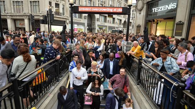 People queue at an entrance to Oxford Circus station, London