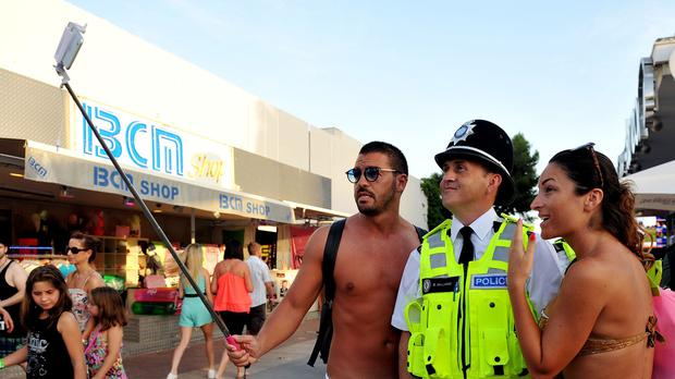 A couple pose for a selfie with West Midlands Police officer Sergeant Brett Williams in Magaluf