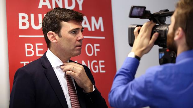 Labour leadership candidate Andy Burnham adjusts his tie before an interview in Westminster