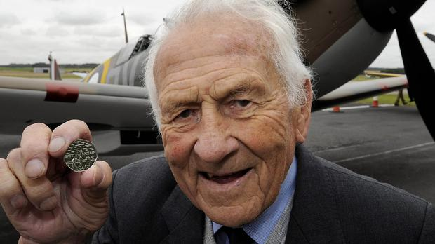 Squadron Leader Tony Pickering inspects The Royal Mint's Battle of Britain 50p commemorative coin, with a Mark I Spitfire in the background