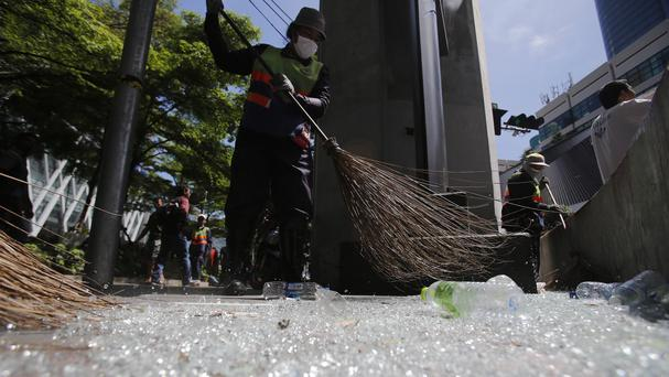 Thai workers sweep broken glass near the Erawan Shrine at Rajprasong intersection in Bangkok following an explosion which killed 20 people (AP)