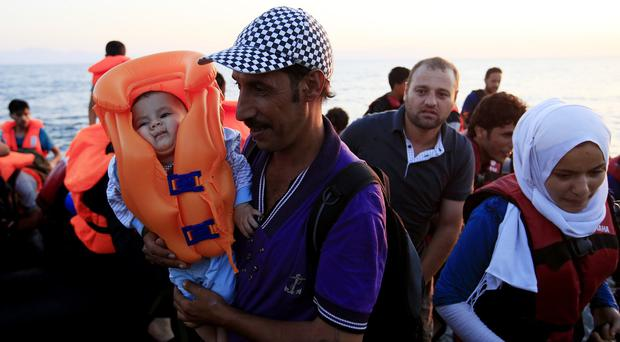 A migrant carrying an eight-month-old child arrives with fellow travellers on the beach at Psalidi near Kos Town, Kos