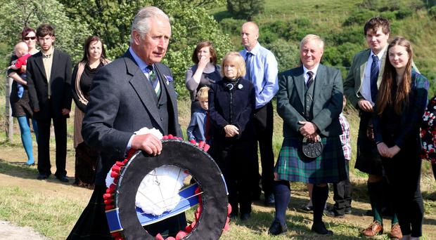 The Prince of Wales lays a wreath during a visit to Cabrach Cairn, Scotland
