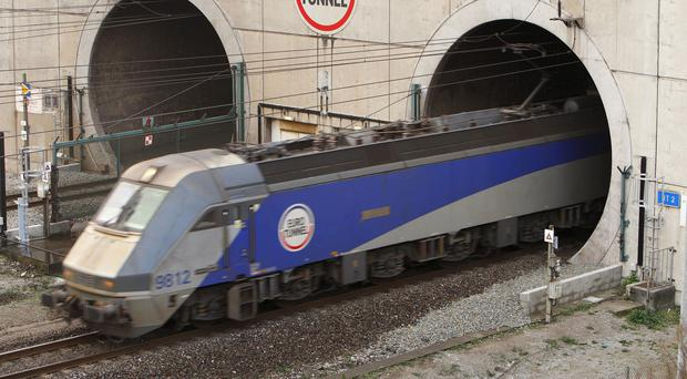 Eurotunnel services were delayed after migrants sneaked on to a freight train headed for the UK