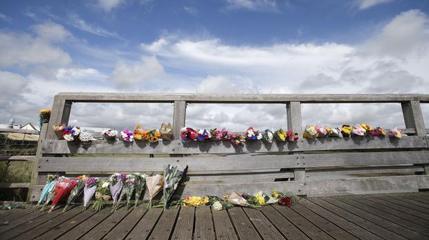 Flowers laid on the Shoreham Tollbridge over the River Adur near the site where an historic Hawker Hunter fighter jet plummeted on to the A27