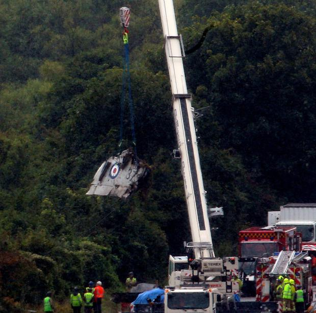 Horror: a crane is used to remove wreckage of the Hunter jet which crashed in Shoreham