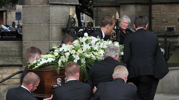 Gary and Phil Neville join other pall bearers to carry the coffin of their father Neville Neville into Bury Parish Church in Greater Manchester