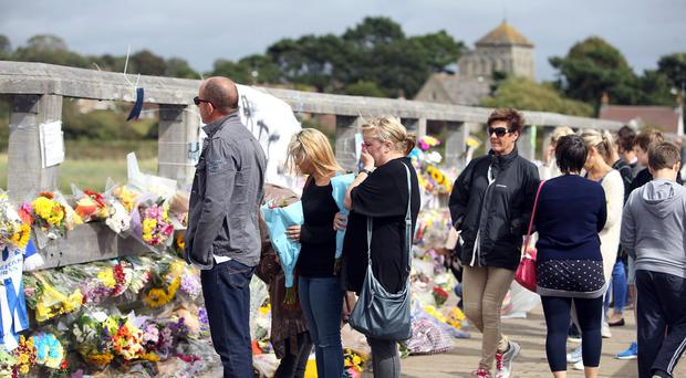 People look at floral tributes left on the Old Tollbridge near the A27 at Shoreham in West Sussex after last week's crash
