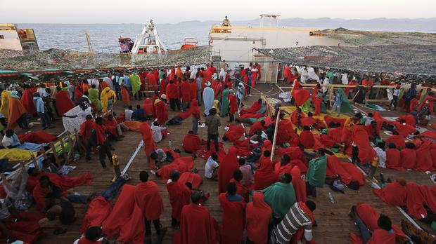 Rescued migrants on the deck of the Norwegian Siem pilot ship as they approach the Italian port of Cagliari (AP)
