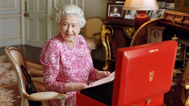 The Queen, seated at her desk at Buckingham Palace with one of her official red boxes which she has received almost every day of her reign, in a photo taken by Mary McCartney