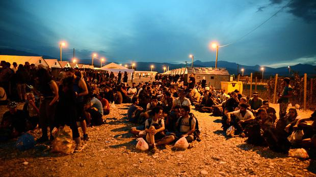 People sit on the ground at a refugee camp in the southern Macedonian town of Gevgelija (AP)
