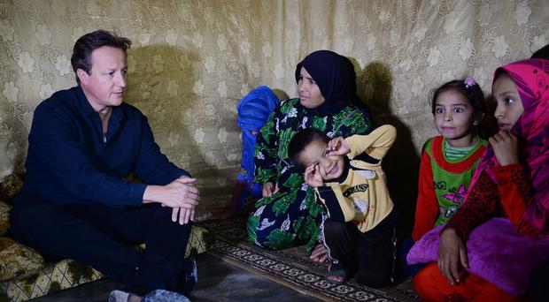 David Cameron meets Syrian refugee families at a tented settlement camp in the Bekaa Valley on the Syrian - Lebanese border.