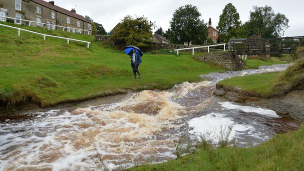 A man walks by the fast flowing beck in Hutton le Hole, North Yorkshire, after heavy rain
