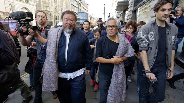 Artists Ai Weiwei (left) and Sir Anish Kapoor carry a single blanket as a symbol of the need that faces 60 million refugees
