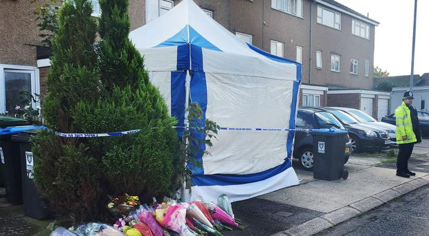 A police officer stands outside the house in Hemel Hempstead, Hertfordshire, where Nicola Cross, 37, was stabbed to death