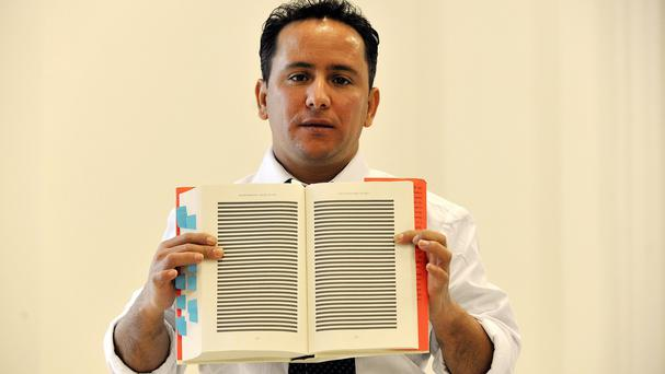 Yahid Ould Slahi holds open Guantanamo Diary - showing redacted pages - written by his brother Mohamedou Ould Slahi