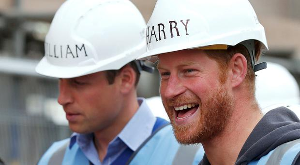 Prince Harry (right) with Prince William, Duke of Cambridge, as they tour a building site in Manchester as part of their visit to the BBC's DIY SOS television show, helping to renovate homes for ex-service personnel