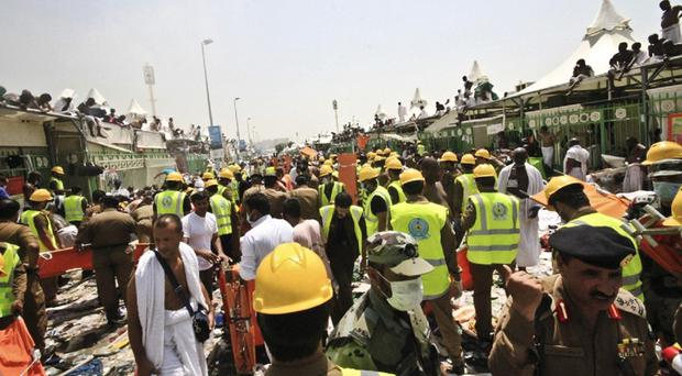Pilgrims and rescuers rush to the aid of people crushed in the stampede in Mina (AP)