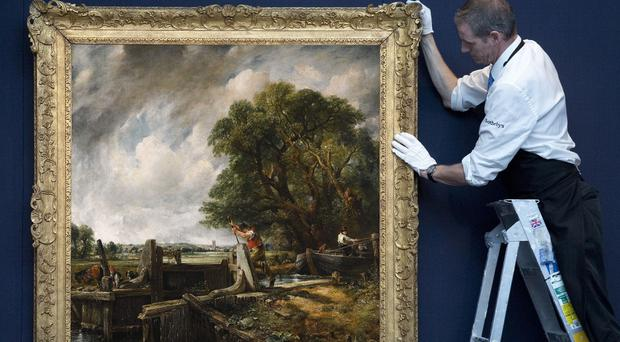 A gallery technician hanging The Lock by John Constable (Sotheby's)